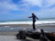 Elise joue à l'equilibriste sur une plage de la côte Ouest
