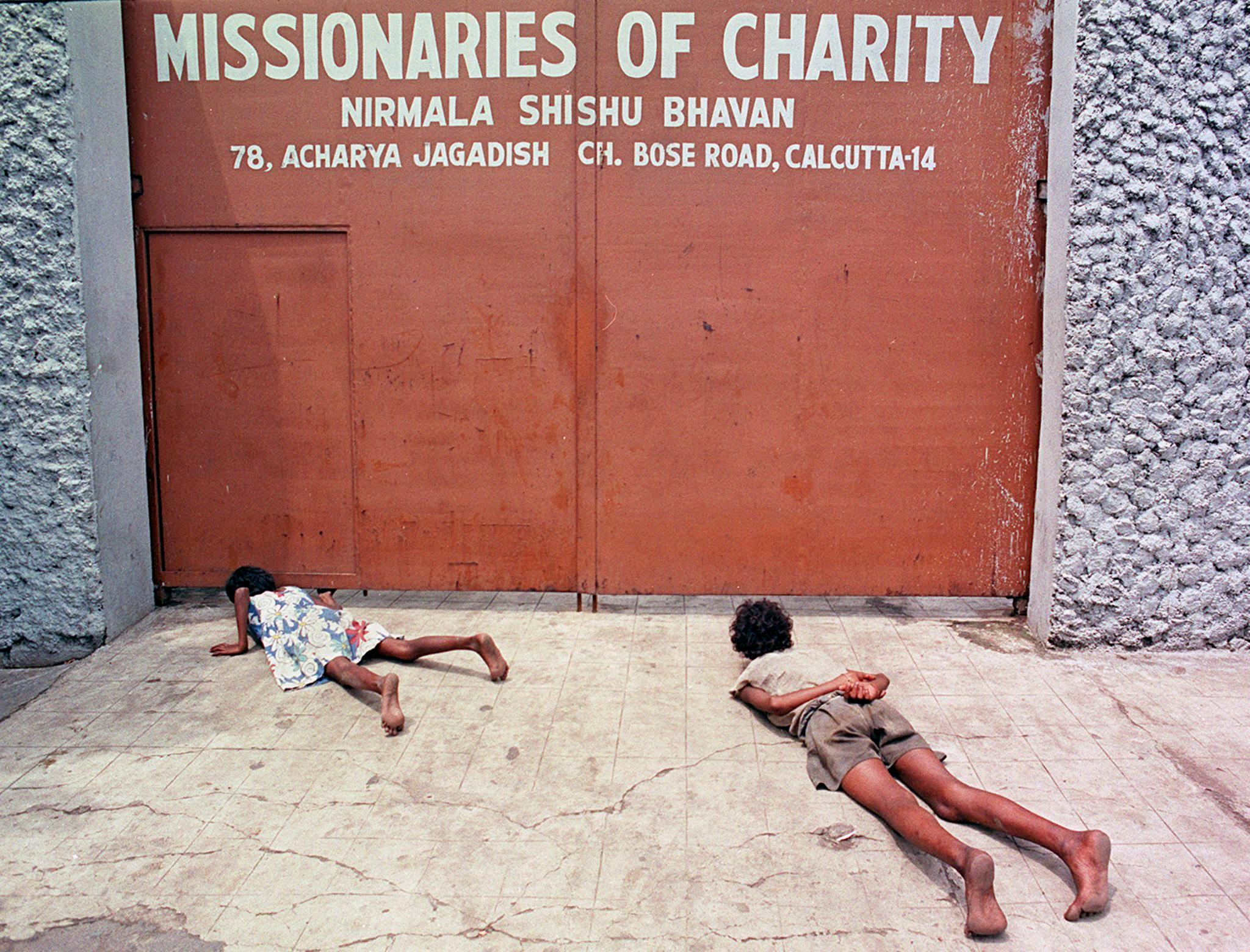A young girl and a man crawl on the ground to peep underneath the gate to the Missionaries of Charity.