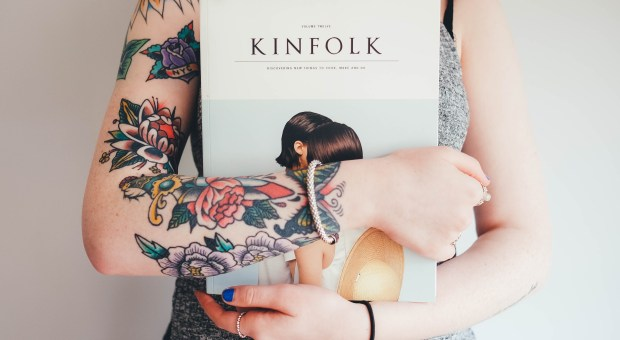 A tattooed woman holds a copy of Kinfolk magazine