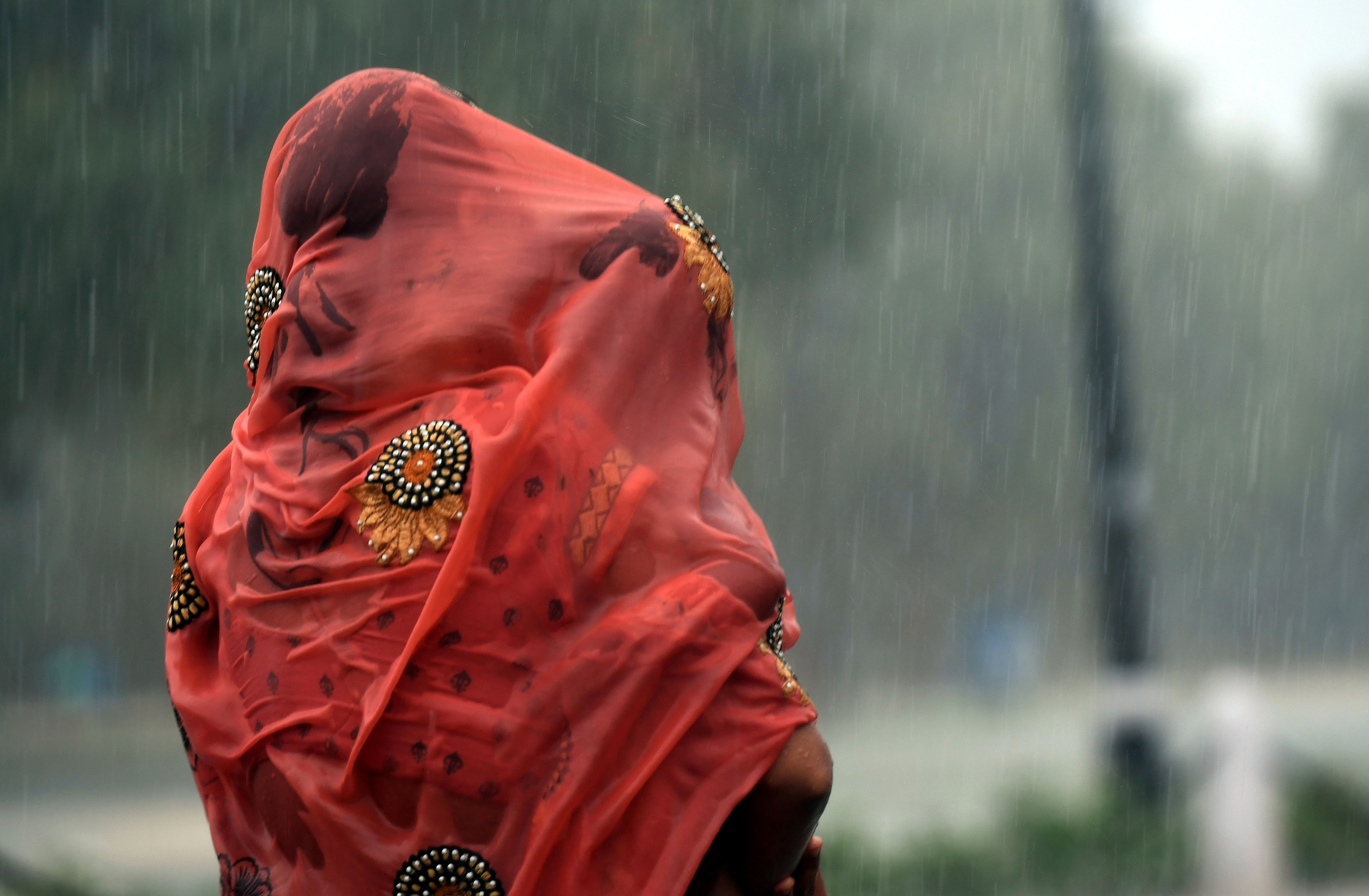 An Indian woman covers her baby under her saree during heavy rain at Rajpath in New Delhi on August 7, 2017. (Photo: PRAKASH SINGH/AFP/Getty Images)