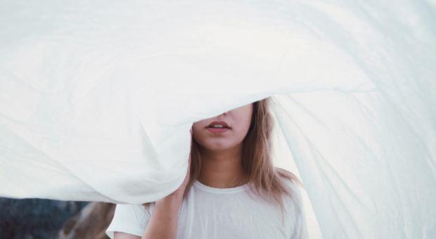 Woman wrapped in sheet. Photo by Yoann Boyer.
