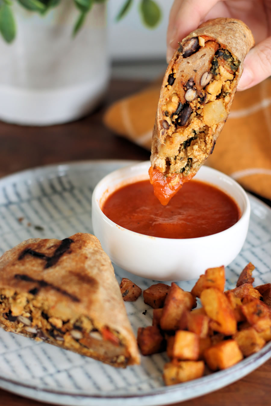 dipping the Veestro Breakfast Burrito in red sauce