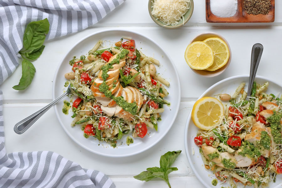 Two Plates of Chicken Basil Pesto Pasta served with lemon