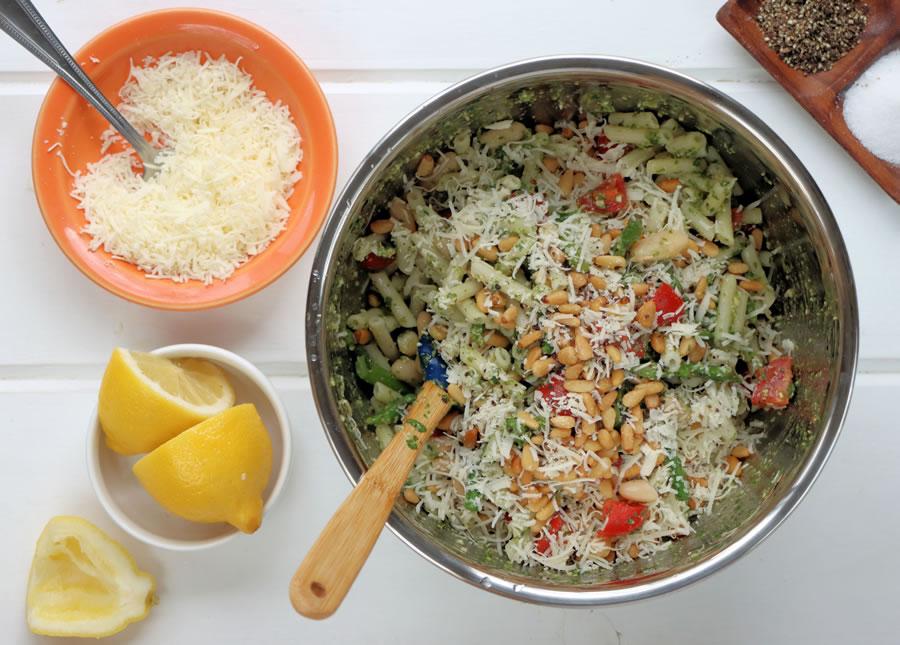 Stirring the pesto pasta ingredients in a big metal bowl