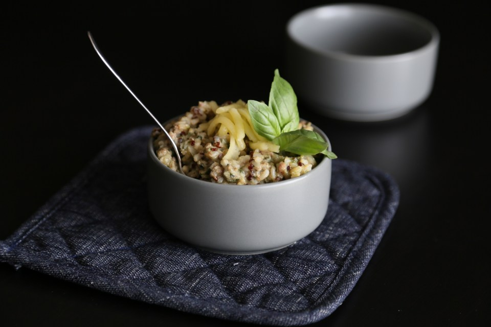 Spinach, turkey and mushroom risotto in a bowl with a spoon.