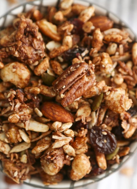 A bowl full of homemade chocolate granola on a striped tablecloth.