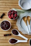 Homemade berry jam on spoons and in bowl.