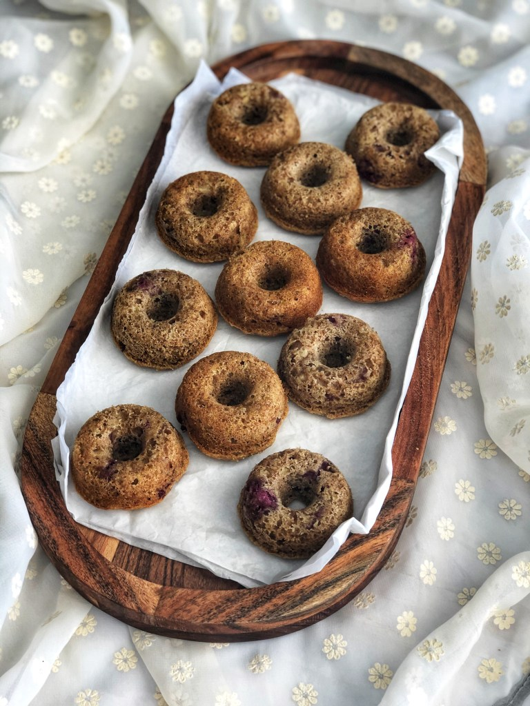 Zucchini donuts on a wooden platter.