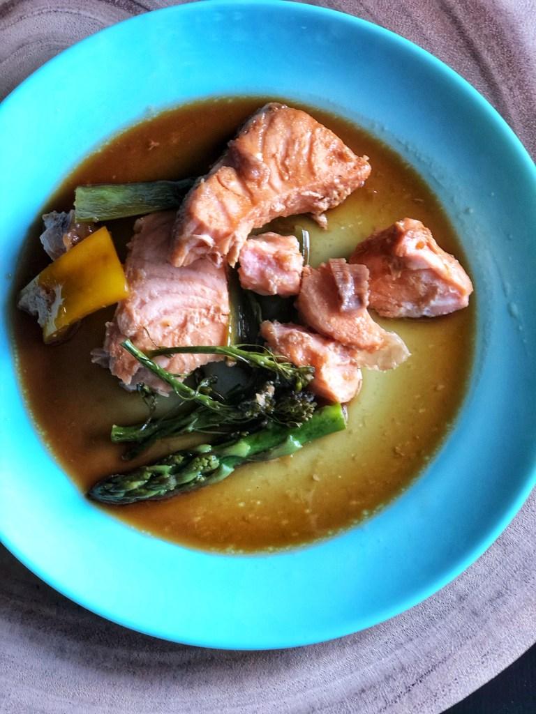 Easy steamed teriyaki salmon on a blue plate.