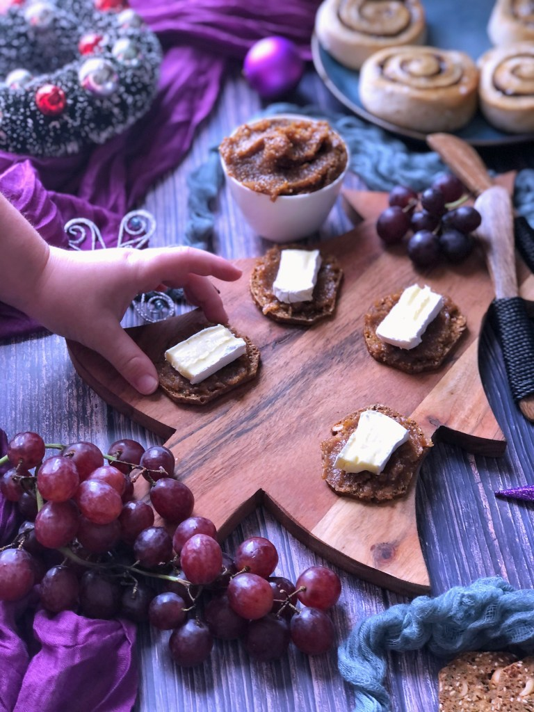 A child's hand reaching for a biscuit with fig jam and a slice of brie.