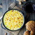 A bowl of delicious cheesy leeks served with crusty brown bread