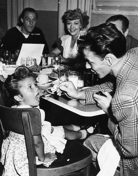 Frank feeds Nancy at MGM Commissary during a break from shooting ANCHORS AWAY. Gene Kelly looks on