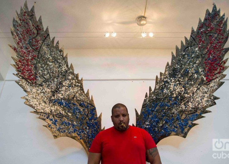 Cuban artist Michel Mirabal along with works of the personal exhibition that he is exhibiting in his gallery workshop, as part of the collateral activities of the 13th Havana Biennial. Photo: Otmaro Rodríguez.