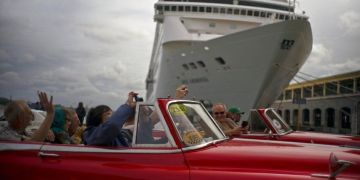 Tourists touring Havana pass in front of a cruise ship docked in the port of the Cuban capital. Photo: Ramón Espinosa / AP.