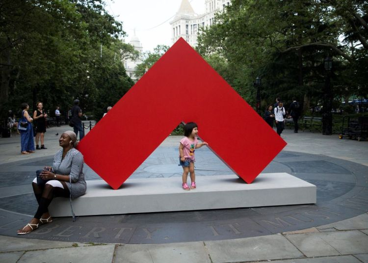 Passers-by interact with a work of the first great exhibition of outdoor sculptures by Cuban artist Carmen Herrera in New York. Photo: Kena Betancur / EFE.