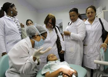 Cuban doctors observe a dental procedure during a training session at a health clinic in Brasilia. Photo: Eraldo Peres / AP.