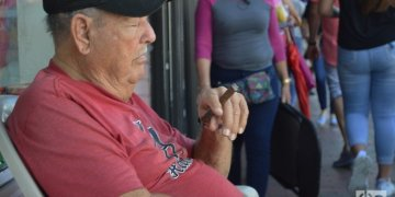 A Cuban smokes a cigar and dozes in front of his business on Calle Ocho. Photo: Marita Pérez Díaz.