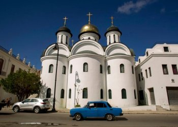 A Moskvitch car from the Soviet era circulates in front of the Russian Orthodox Cathedral in Havana. Photo: Ismael Francisco / AP.