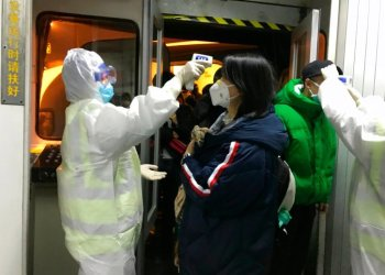 Health officials check the body temperature of passengers arriving from Wuhan City to Beijing Airport on Wednesday, January 22, 2020. Photo: AP / Emily Wang.
