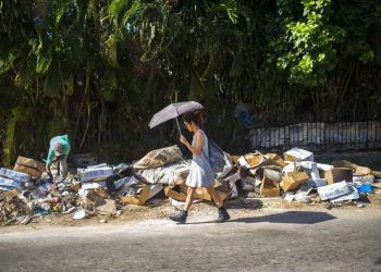 A woman walks next to a pile of garbage in the Vedado neighborhood of Havana, Cuba. Photo: Desmond Boylan/AP/Archive.