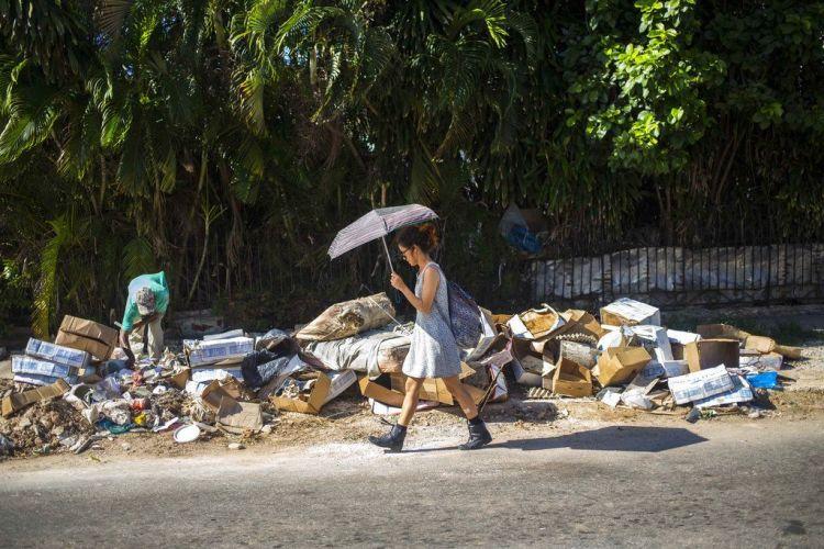 A woman walks next to a pile of garbage in the Vedado neighborhood of Havana, Cuba. Photo: Desmond Boylan/AP/Archive.