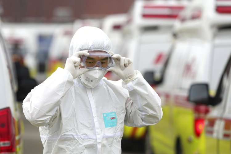 A health worker with protective clothing adjusts his glasses before moving patients in Daegu, South Korea, on Sunday, March 1, 2020. Photo: Ryu Young-seok/Yonhap via AP.