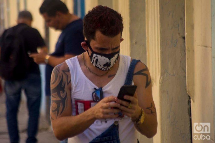 A Cuban checks his cell phone using a facemask in Havana, as a protection measure against the COVID-19 pandemic. Photo: Otmaro Rodríguez.