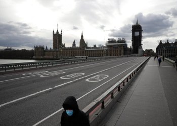 A person with a face mask walks across the nearly empty Westminster Bridge with Parliament in the background. London, Friday March 20, 2020. Photo: Matt Dunham/AP.