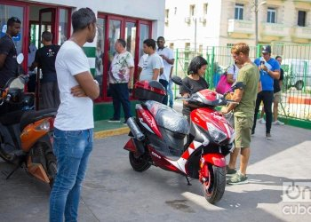 A couple by an electric motorcycle purchased at El Tángana gas station, in Havana, on October 28, 2019. Photo: Otmaro Rodríguez.