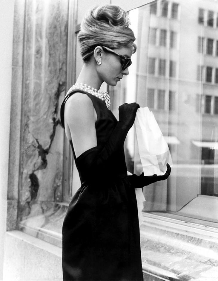 """El vestido negro sin mangas que usó Audrey Hepburn en """"Breakfast at Tiffany's"""", combinado con hileras de perlas, guantes hasta los codos y enormes gafas de sol, terminó convirtiéndose en el look más famoso del diseñador."""