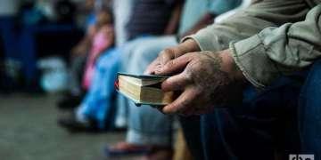 Un cubano sostiene una biblia mientras escucha la misa. Foto: Irina Dambrauskas.