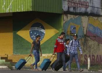 Venezolanos avanzan con su equipaje tras cruzar la frontera entre Brasil y Venezuela en la ciudad de Pacaraima, estado brasileño de Roraima, en marzo de 2018. Foto: Eraldo Peres / AP.
