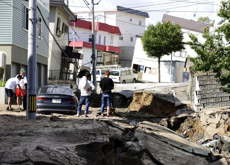 Residentes observan una carretera dañada por un sismo en Sapporo, Hokkaido, en el norte de Japón, el 6 de septiembre de 2018. Foto: Hiroki Yamauchi / Kyodo News vía AP.