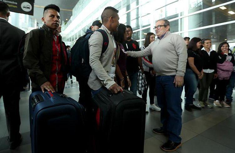 El máximo líder de las FARC, Rodrigo Londoño (d), saluda a jóvenes colombianos que parten hacia Cuba a estudiar medicina os de las FARC, víctimas del conflicto y exmiembros de la fuerza pública viajan a Cuba para estudiar medicina, como parte del acuerdo de paz y con el apoyo de la Unión Europea. Foto: Mauricio Dueñas Castañeda / EFE.
