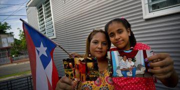 Lady Diana (izq) y su hija Paula Nicole López posan con fotos del esposo de Diana y padre de Paula, Orlando López, quien padecía de dieabetes y falleció a los 48 años al no recibir suficientes tratamientos de diálisis después del paso del huracán María por Puerto Rico. Foto: Ramón Espinosa / AP.
