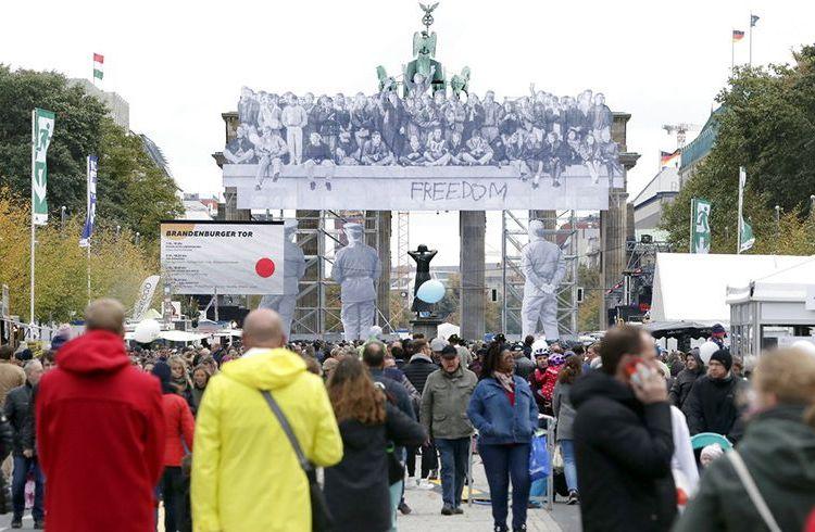 Visitantes caminan frente a la Puerta de Brandenburgo durante los festejos del Día de la Unificación en Berlín, Alemania, el miércoles 3 de octubre de 2018. Foto: Michael Sohn / AP.