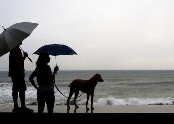 Una pareja y su perro, parados en la orilla antes de la llegada del huracán Willa, en Mazatlan, México, el 23 de octubre de 2018. Foto: Marco Ugarte / AP.