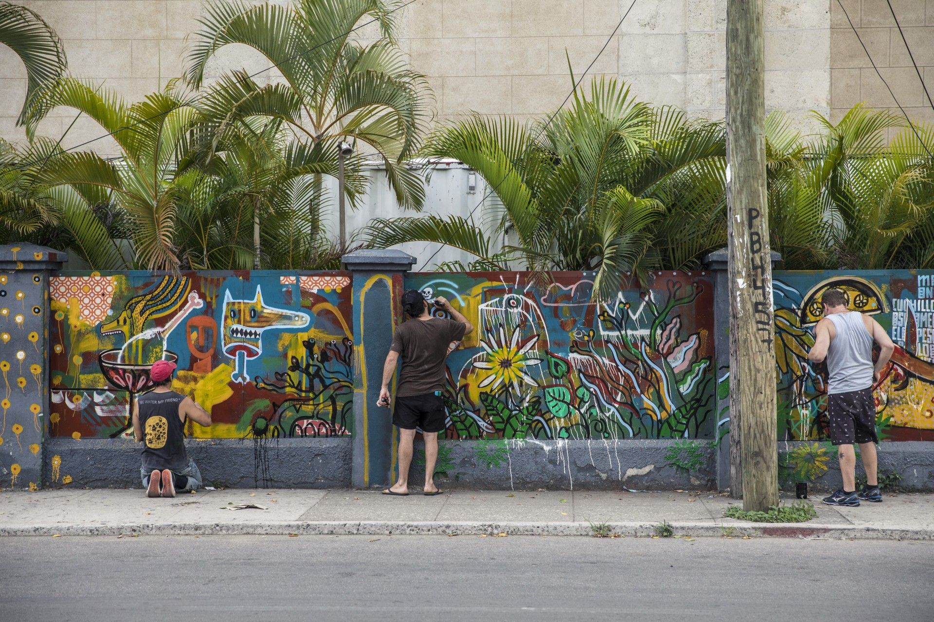 Artistas cubanos y brasileños pintando el mural del muro exterior de FAC. Foto: Cortesía FAC.