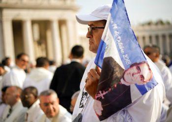 Un hombre sostiene un banderín con la imagen del arzobispo salvadoreño Oscar Romero antes de la ceremonia de canonización en su honor, en la Plaza de San Pedro en el Vaticano, este domingo 14 de octubre del 2018. Foto: Andrew Medichini / AP.