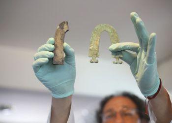 El arqueólogo Jedu Sadarnaga muestra joyas descubiertas en una de las tumbas halladas en un cementerio inca cerca de La Paz, Bolivia, el jueves 15 de noviembre del 2018. (AP Foto/Luis Gandarillas)