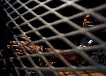 Un hombre que es parte de la caravana de migrantes centroamericanos, dentro de una camioneta de la policía después de ser arrestado, de acuerdo a las autoridades, por fumar marihuana, en Tijuana, México, el miércoles 21 de noviembre de 2018. Foto: Ramon Espinosa / AP.