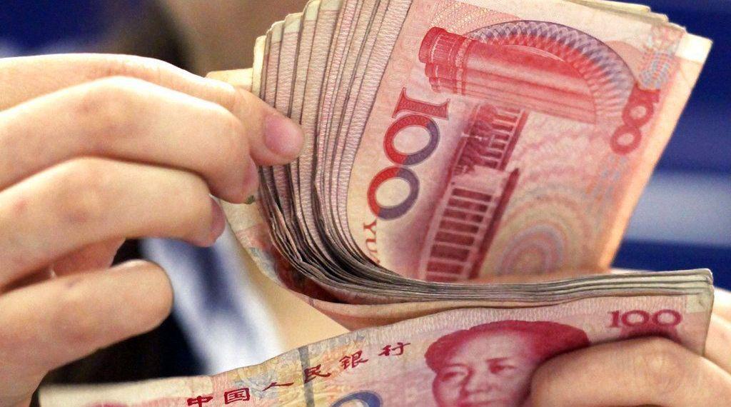 En esta foto del 25 de agosto de 2010, un cajero bancario cuenta billetes de 100 yuan en Shanghái. La moneda china cayó a su nivel más bajo en 22 meses frente al dólar, se informó el jueves 18 de octubre de 2018. (AP Foto/Eugene Hoshiko)