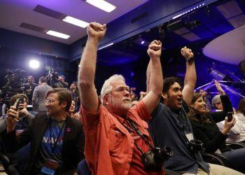 Unas personas en el Laboratorio de Propulsión a Chorro de la NASA en Pasadena, California, celebran mientras la sonda InSight aterriza en Marte el lunes 26 de noviembre de 2018. (AP Foto/Marcio Jose Sanchez)
