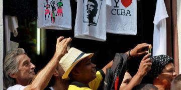 Personas fotografían al presidente Pedro Sánchez mientras recorren calles de La Habana. Foto: Yander Zamora / EFE.