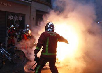 Bomberos intentan extinguir el fuego de un vehículo incendiado por manifestantes durante un enfrentamiento con policías antidisturbios en París, el sábado 8 de diciembre de 2018. Foto: Thibault Camus / AP.