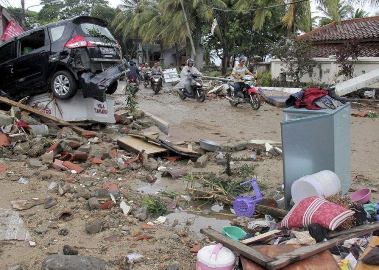 Varios motociclistas avanzan por una calle llena de escombros tras el paso de un tsunami en Anyar, Indonesia, el domingo 23 de diciembre de 23, 2018. Foto: AP.
