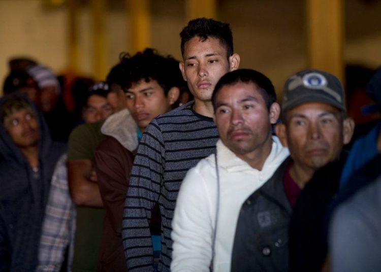 Migrantes hondureños hacen línea para tomar desayuno en un depósito que abrió sus puertas para dar de comer a los migrantes en el centro de Tijuana, México, el martes 18 de diciembre del 2018. Foto: Moisés Castillo / AP.