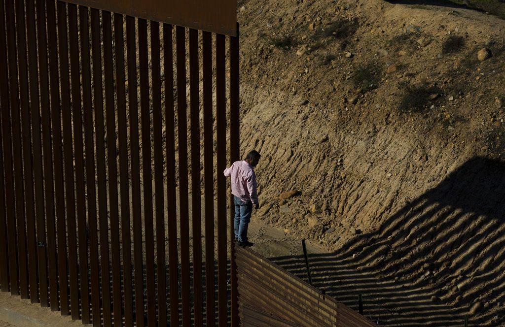 Un migrante se para en la valla fronteriza antes de saltar al lado de Estados Unidos, hacia San Diego, California, desde Tijuana, México, el viernes 28 de diciembre de 2018. Foto: Daniel Ochoa de Olza / AP.