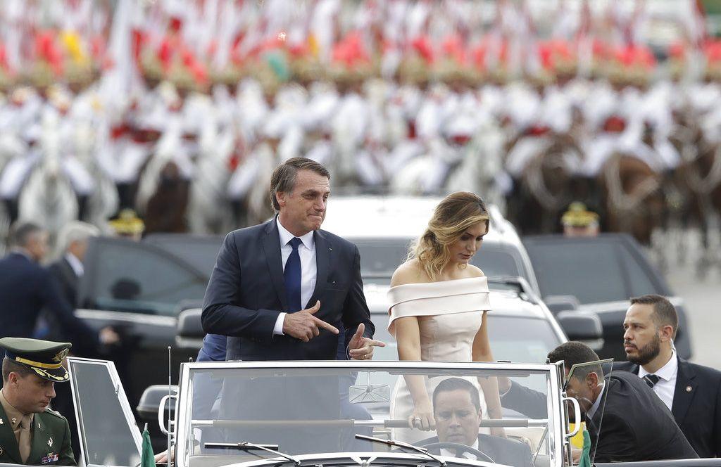 Acompañado por la primera dama Michelle Bolsonaro, el presidente de Brasil, Jair Bolsonaro, se desplaza en un auto abierto después de su ceremonia de investidura el martes 1 de enero de 2019 en Brasilia. Foto: André Penner / AP.
