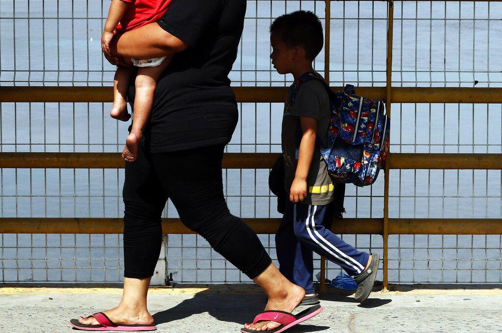 Una madre y sus dos hijos caminan sobre el puente del río Suchiate, parte de un grupo de migrantes centroamericanos que cruzaron la frontera entre Guatemala y México, cerca de Ciudad Hidalgo, estado de Chiapas, México, el jueves 17 de enero de 2019. (AP Foto/Marco Ugarte)
